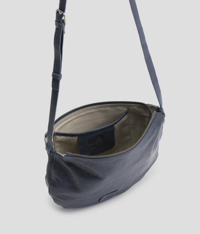 Bolso bandolera de piel color azul oscuro de forma media luna. Tiene la tira regulable y cierra con cremallera. El bolso que siempre llevarás