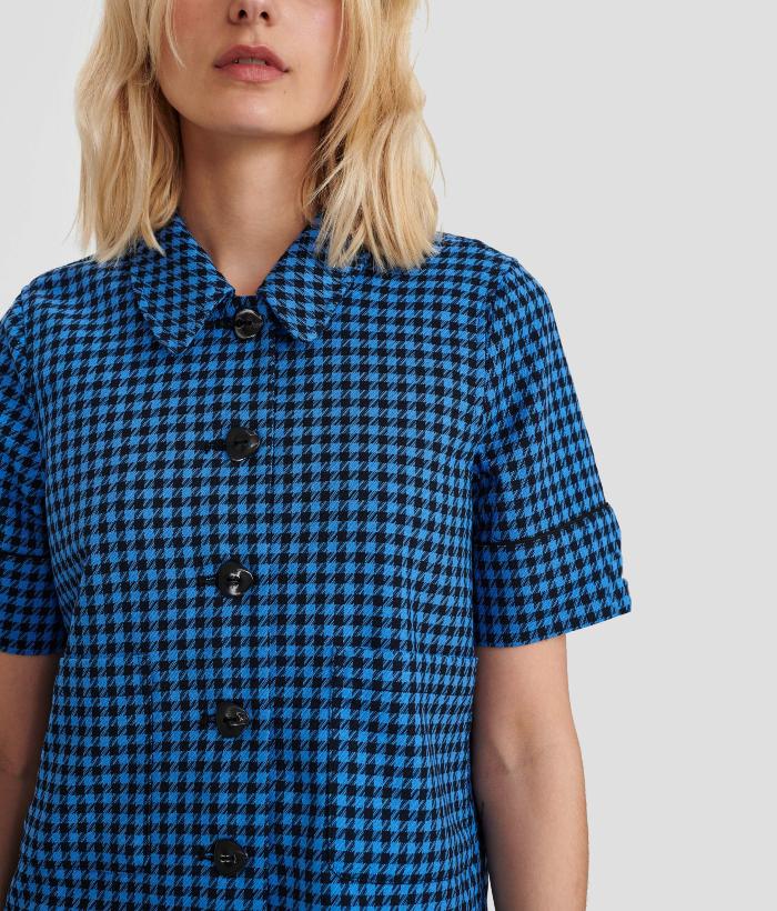 Chaqueta manga corta de cuadros vichy negros y azules con bolsillos plastón y botones negros grances de la marca Nümph.